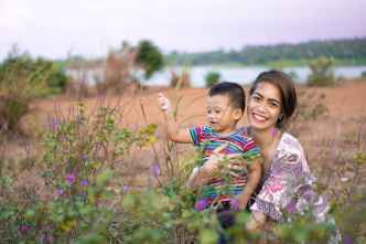 woman hugging boy on field